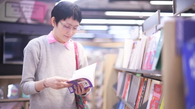 Asian woman shopping for book at shopping mall