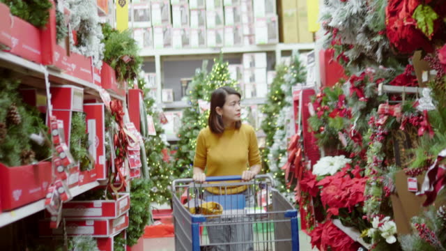 vídeos de stock e filmes b-roll de asian woman shopping for christmas at the supermarket - feriado