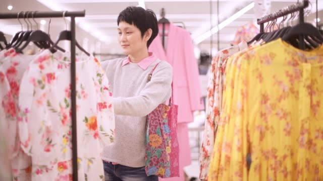 Asian woman shopping for clothes at shopping mall