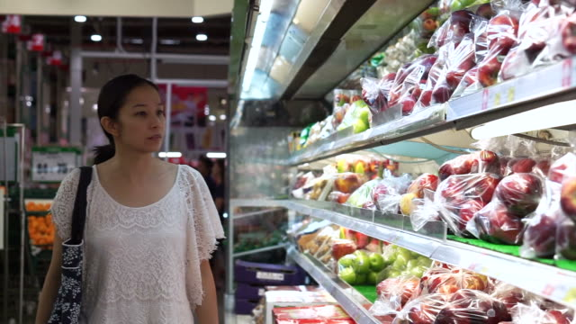 Asian woman shopping for fruits in supermarket isle video