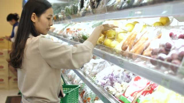 vídeos y material grabado en eventos de stock de mujer asiática compras frescas frutas y verduras en supermercado - eventos de etiqueta