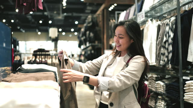 Asian woman Shopping in Clothing Store at Shopping Mall