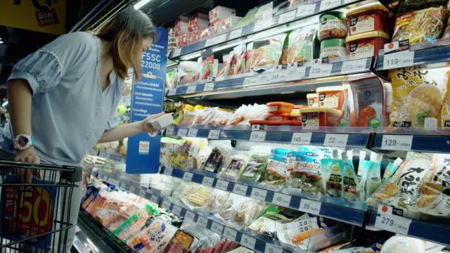 asiatische frau beim einkaufen im supermarkt - gefrierkost stock-videos und b-roll-filmmaterial
