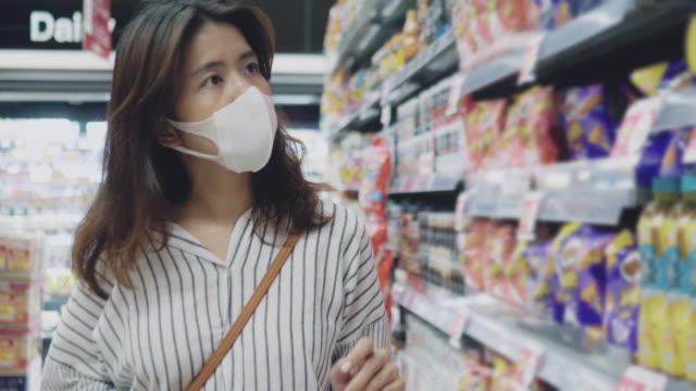 yüz maskesi koruması ile süpermarkette asyalı kadın alışveriş - maske stok videoları ve detay görüntü çekimi