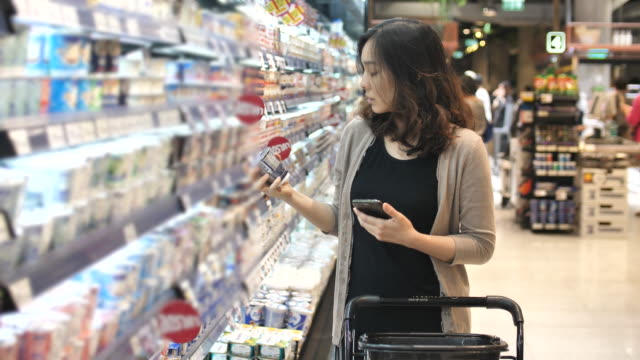 asian woman shopping in supermarket with smart phone, slow motion - borsa della spesa video stock e b–roll