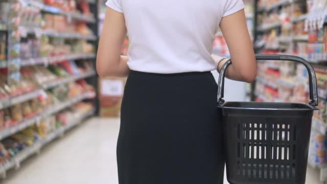 asiatisk kvinna shopping i snabbköpet, slow motion - dagligvaruhandel, hylla, bakgrund, blurred bildbanksvideor och videomaterial från bakom kulisserna
