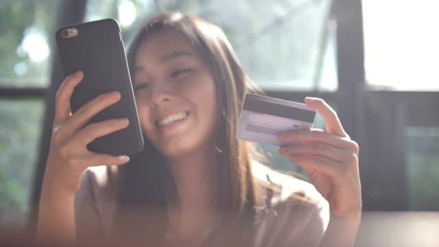 アジアの女性ショッピングオンラインスマートフォンでクレジットカード - 通販点の映像素材/bロール