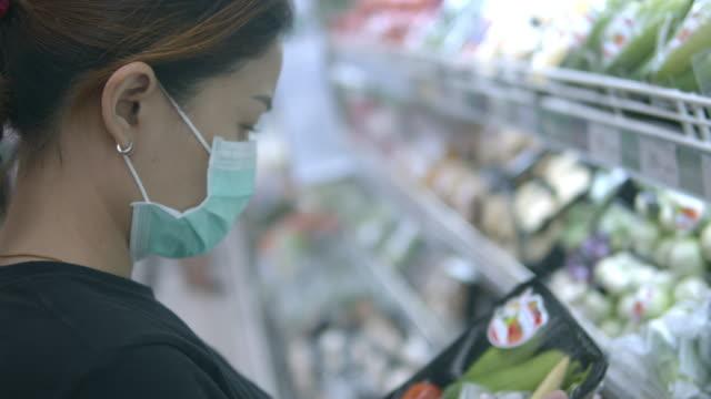 asian woman shopping withface maskp rotection from corona virus(covid-19) - mercato frutta donna video stock e b–roll