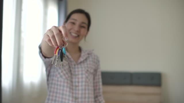 asiatische frau zeigt schlüssel - hypothek stock-videos und b-roll-filmmaterial