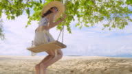 istock Asian woman Sit in a Swing chair at the beach on a clear day 1265568514