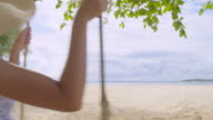 istock Asian woman Sit in a Swing chair at the beach on a clear day 1265609734