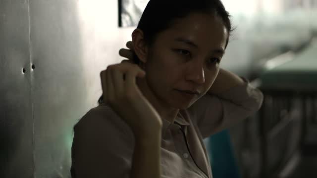 vídeos y material grabado en eventos de stock de mujer asiática sentado solo en el hospital. preocupado y ansioso de pensar malas noticias 4k - servicios sociales