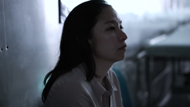 asian woman sitting alone in hospital. worried and  anxious from thinking of bad news 4k - cancer patient stock videos & royalty-free footage