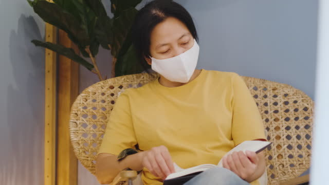 asian woman sitting at wicker chair and reading book at home