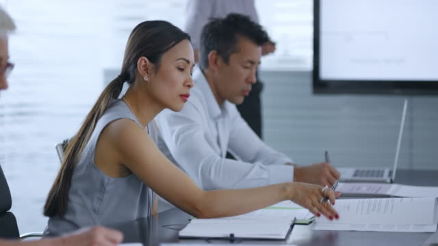 Asian woman sitting in conference room listening to female colleague giving a presentation video
