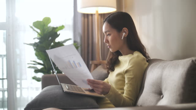 Asian Woman Sitting on Sofa and using laptop at home Laptop, Home Asian Woman Sitting on Sofa and using laptop at home chinese culture stock videos & royalty-free footage