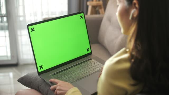 亞洲 婦女坐在 sofa 使用筆記型電腦與綠屏 在家裡 - laptop 個影片檔及 b 捲影像