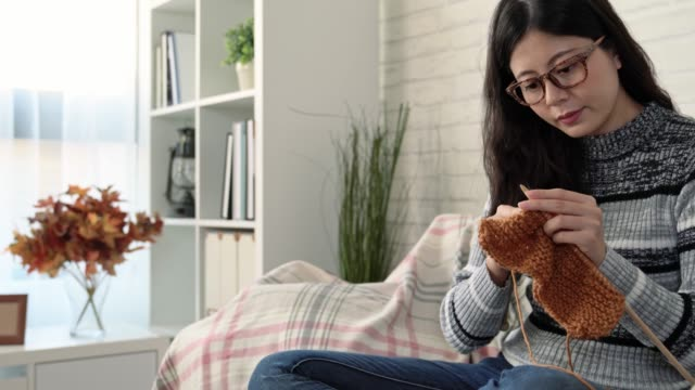 Asian woman sitting on the sofa and knitting