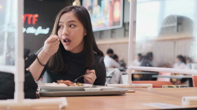 Asian woman sitting separated in restaurant eating food .keep social distance for protect infection from coronavirus covid-19, restaurant and social distancing concept.