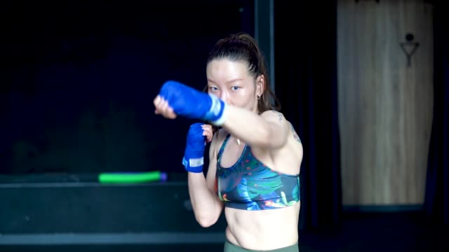 Asian woman slow motion shadowboxing training in gym.