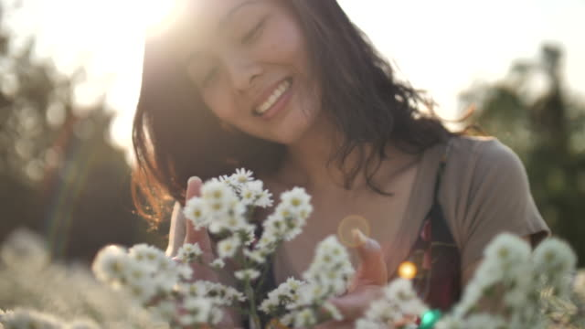 Asian Woman smelling at flowers Asian Woman smelling at flowers bunch stock videos & royalty-free footage
