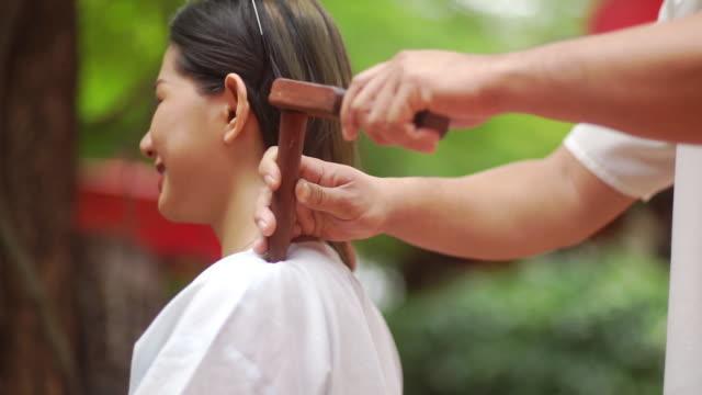 asiatische frau lächelnd und genießen mit thai traditionellen hammer massage von professionellen masseur. - sauna und nassmassage stock-videos und b-roll-filmmaterial