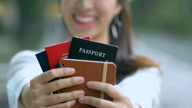 Asian woman smiling and holding passport with tickets Asian woman smiling and holding passport with tickets passport stock videos & royalty-free footage
