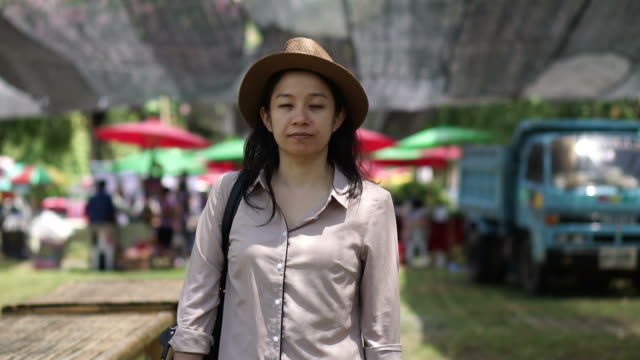 Asian woman smiling wearing hat standing local farmer market. Buy organic and home grown product from community video
