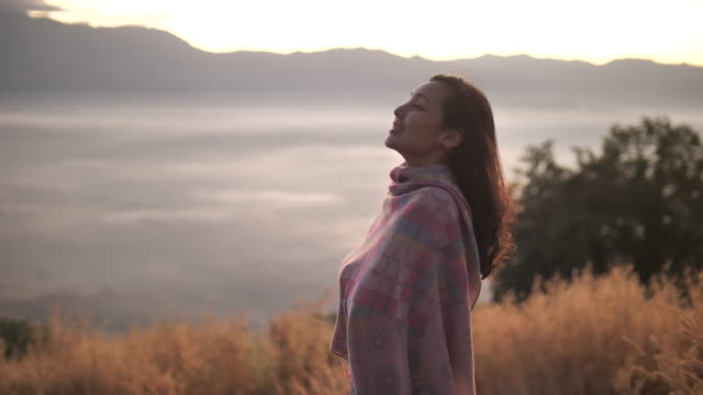 Asian Woman standing on top of mountain, enjoying breathtaking view at sunset