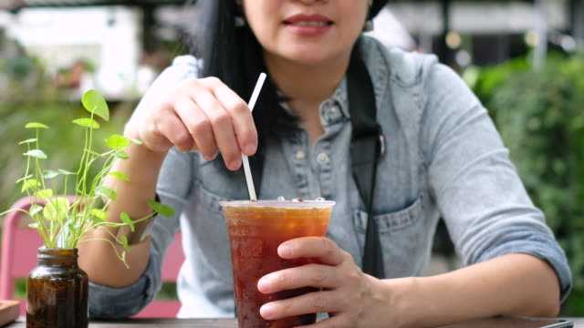 asian woman stirring ice tea at coffee shop in sunny day.summer drink