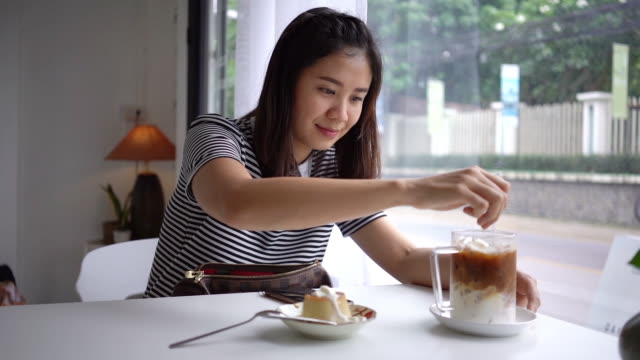 vídeos de stock e filmes b-roll de asian woman stirring tasty ice coffee. - café gelado