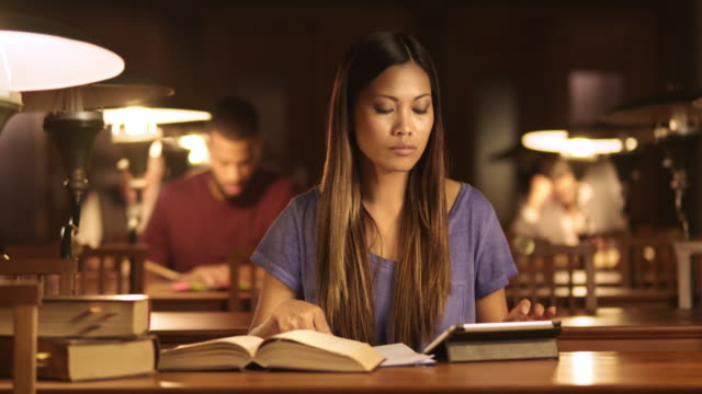 DS Asian woman studying in library at night video