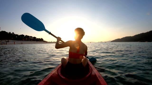 asiatische frau schwimmt im kajak in den sonnenuntergang am lipe, satun, thailand - kanu stock-videos und b-roll-filmmaterial