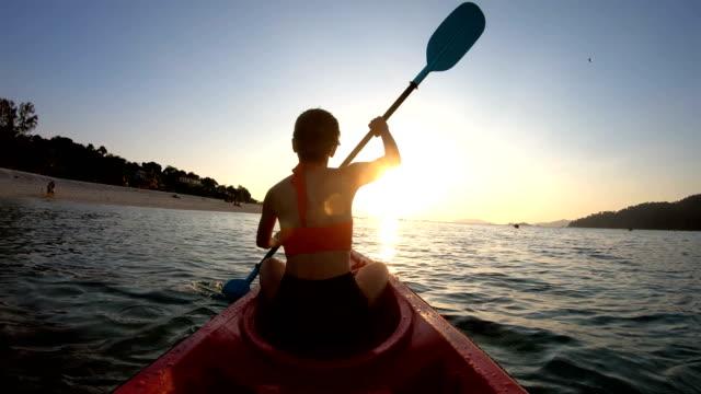vídeos y material grabado en eventos de stock de mujer asiática nada en el kayak en la puesta de sol en lipe, satun, tailandia - kayak