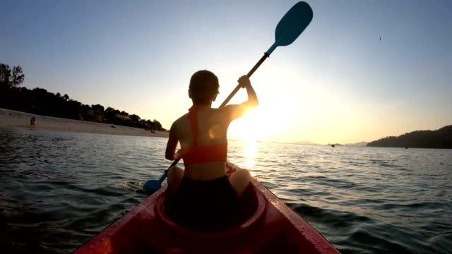 asiatische frau schwimmt im kajak in den sonnenuntergang am lipe, satun, thailand - kajakdisziplin stock-videos und b-roll-filmmaterial