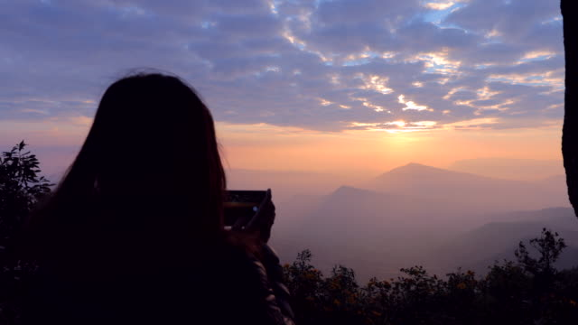 asian woman taking a photo of mountain view with foggy by smartphone , concept woman solo travel - young singles stock videos and b-roll footage