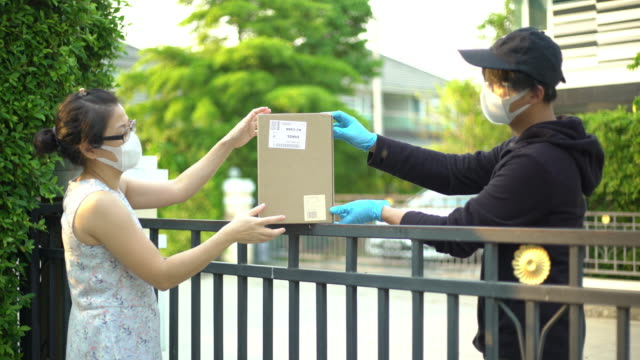asian woman taking package from delivery man wearing face mask and glove for protecting coronavirus covid-19 - igiene video stock e b–roll