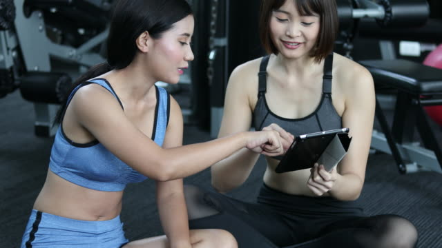 vídeos de stock e filmes b-roll de 2 asian woman talking in gym with tablet - roupa desportiva