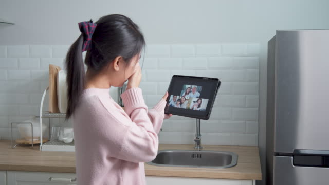 Asian woman talking with family on video call webcam in kitchen room at home while working from home. Self-isolation, social distancing, quarantine for protection coronavirus in next or new normal.