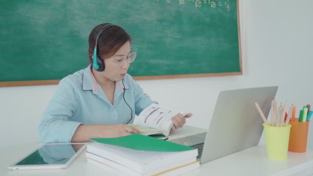 Asian woman teacher book read-a-loud for preschoolers via video conference e-learning in laptop with blackboard at classroom. Homeschooling and distance learning ,online ,education and internet.