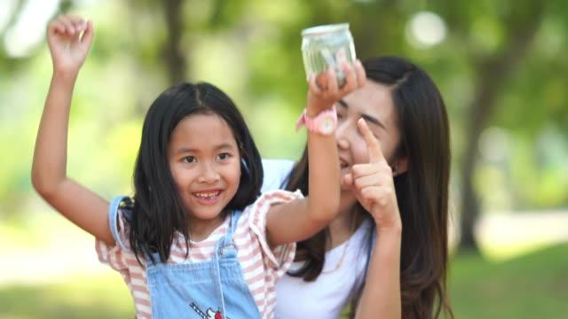 Asian woman teaching girl about saving deposit