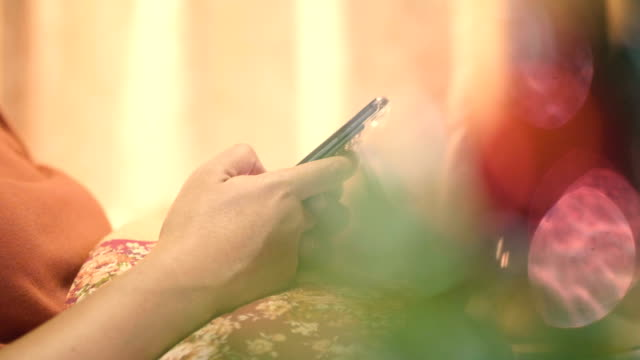 クリスマス ツリーに近いスマート フォンとアジアの女性のテキスト メッセージ - 寂しさ点の映像素材/bロール