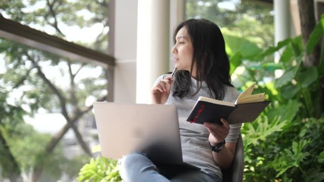vidéos et rushes de femme asiatique pensant recherchant l'idée - travailleur indépendant