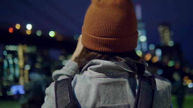 vidéos et rushes de touristique de femme asiatique à l'aide de prendre un panorama photo de rivière de la caméra dans la nuit. - photophone