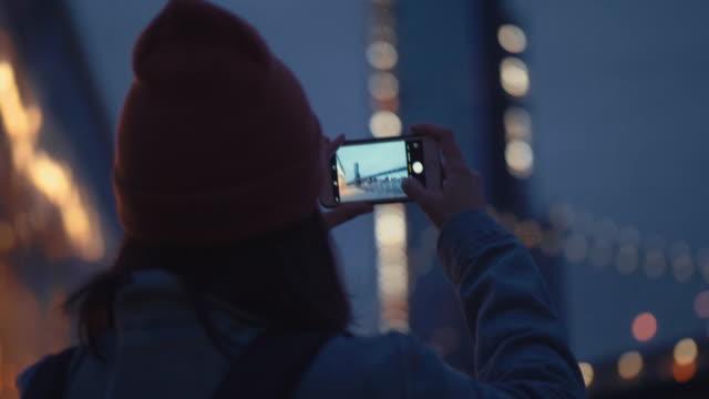 vidéos et rushes de touristique de femme asiatique utilisant smartphone prendre un panorama photo de rivière dans la nuit. - photophone