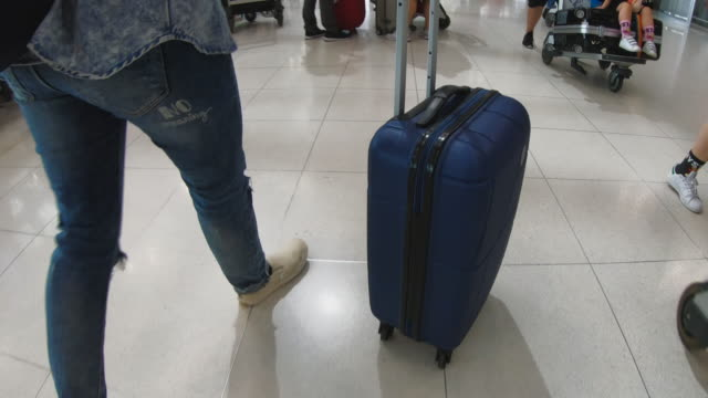 asian woman traveler pulling luggage at airport - donna valigia solitudine video stock e b–roll