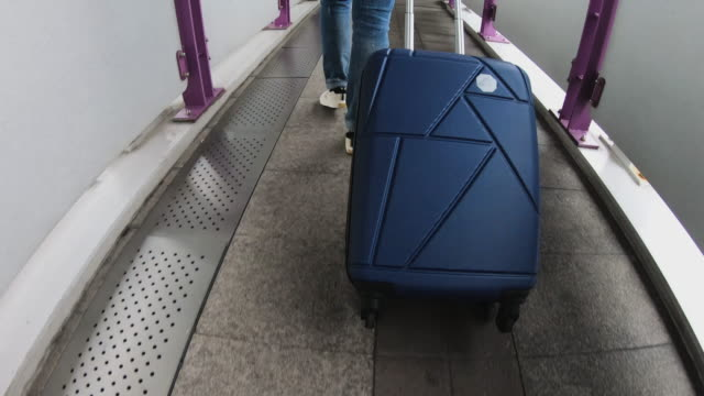 asian woman traveler pulling luggage at transport station travel to airport for vacation - donna valigia solitudine video stock e b–roll