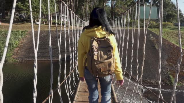 asian woman traveler with backpack walking through rope bridge over water stream - powojnik pnący filmów i materiałów b-roll
