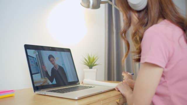 asiatische frau, universität student in der laptop-computer-studie online zu hause. männliche lehrer fernunterricht im internet. e-learning neuer normaler lebensstil oder coronavirus-quarantäne-lockdown-konzept - online lernen stock-videos und b-roll-filmmaterial