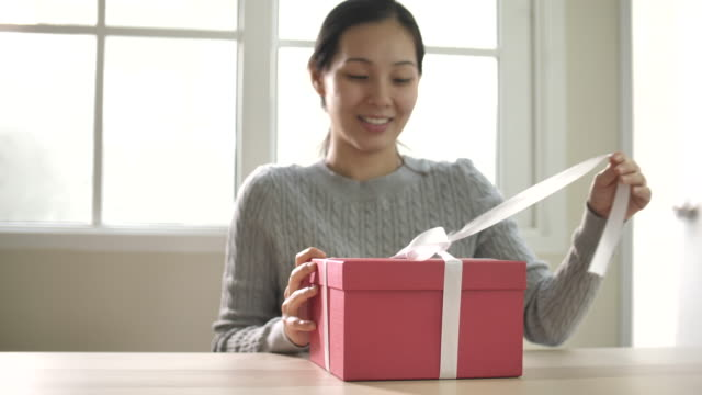 vídeos de stock e filmes b-roll de asian woman unleashes a white bow and opening gift box at home - gift box